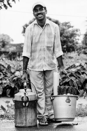 Man carrying bucket and kettle