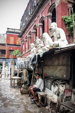 彫像の下に座る男