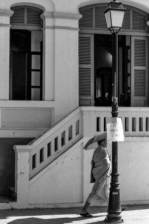 日傘を差して歩く僧侶