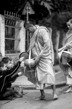 Elderly monk receiving alms