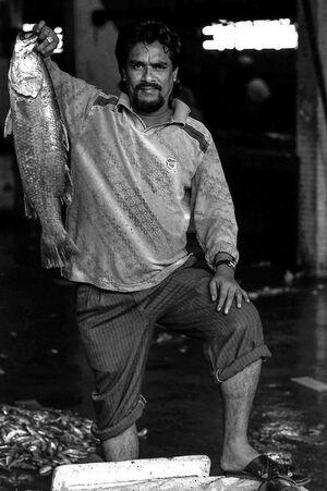 大きな魚を持ち上げる男