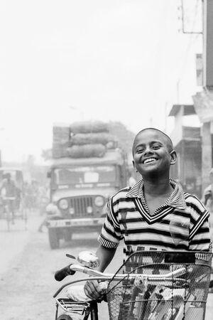 Boy walking bicycle