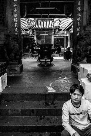 寺院の入口に腰掛ける男