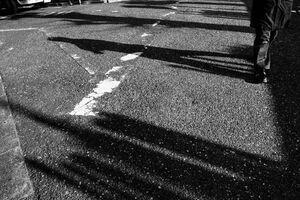 道路の上に落ちた通行人の影