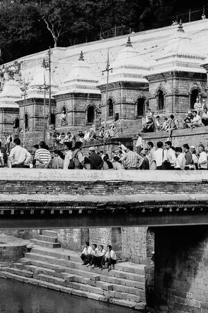 Many people gathering around river in  Pashupatinath Temple