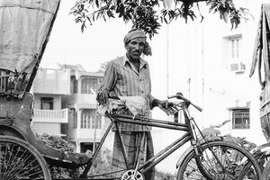 Man standing by cycle rickshaw