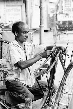 Man repairing a cycle rickshaw