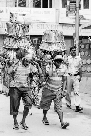 Men carrying metal container