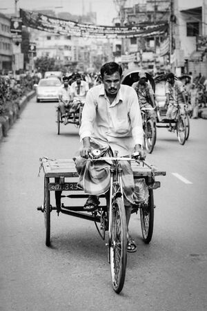 Man pedaling the tricycle with cart