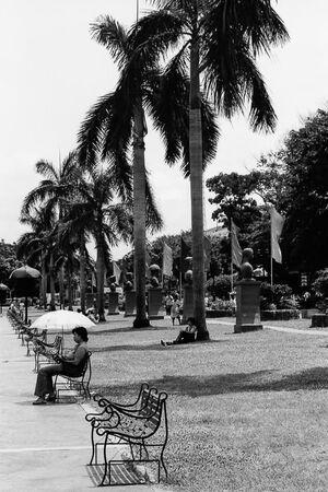 リサール公園のベンチに腰掛けた女