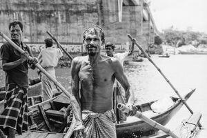 竹製の棹を手にする漕手たち
