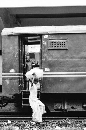 乗降口に立つ男の子と荷物を運ぶ男