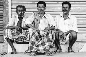 Three men sitting together in front of shutter