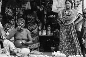 Eating man and standing woman by roadside