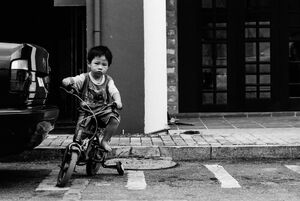 Boy on bicycle with training wheels