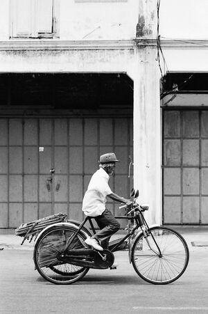 Old man pedaling trishaw