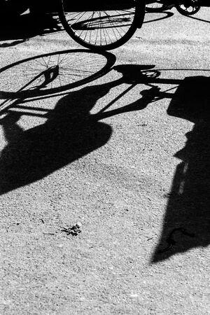 サイクルリクシャーの車輪と脚の影