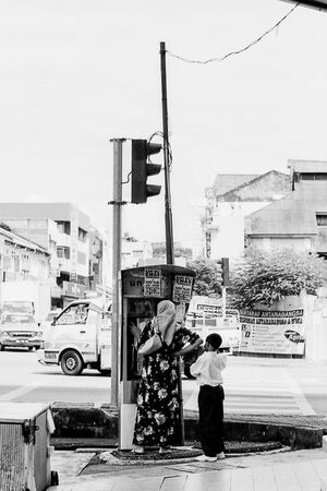 Mother and her son at pay phone