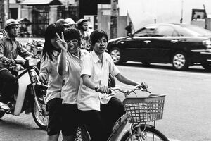Three girls riding on same bicycle