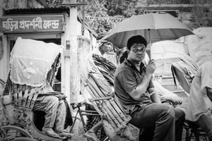 Passenger on cycyle rickshaw putting umbrella up
