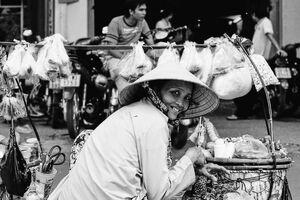 天秤棒を置いた女性の行商人