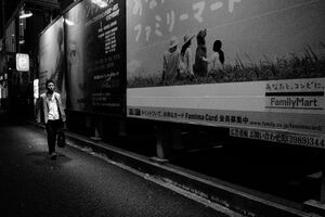 Man walking beside advertisement