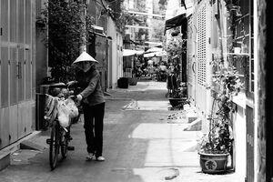 路地を自転車を押して歩く行商人