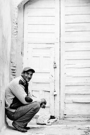 Man sitting in front of locked door