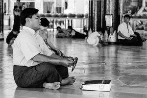 シュエダゴォン・パヤーで数珠を手に祈る男