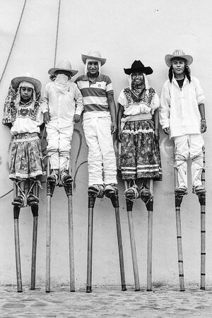 Boys wearing tall stilts