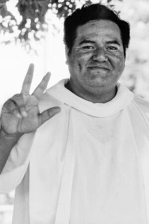 三本指のピースをする神父
