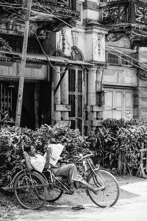 自転車タクシーの座席で寛ぐ男