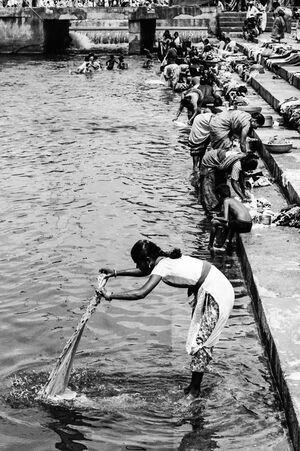 川で洗濯する女
