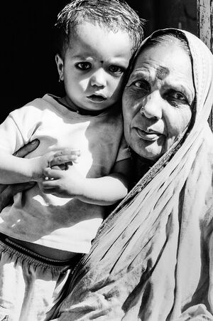 Older woman and little girl putting Bindi