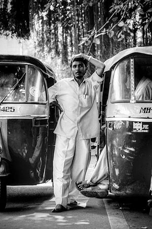 Man between auto rickshaws