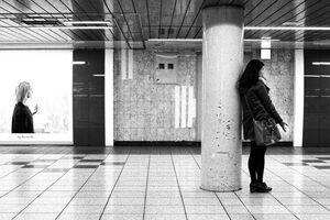 柱の横に立って電話する若い女性