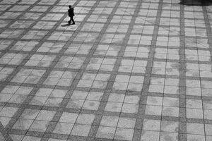 広い広場を歩く男