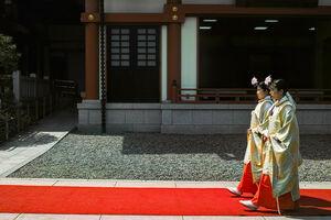 Two Shinto priestesses walking