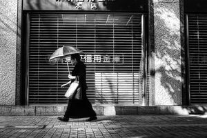 Older woman putting umbrella up