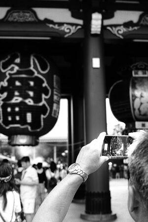 スマホで写真を撮る男