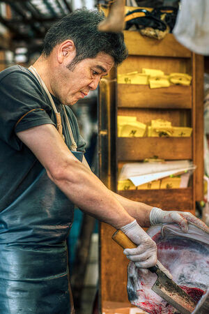 Man cutting head of tuna