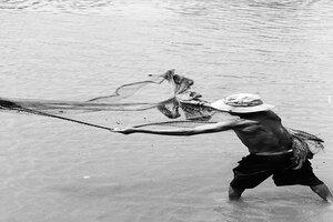 川の中で投網をする男