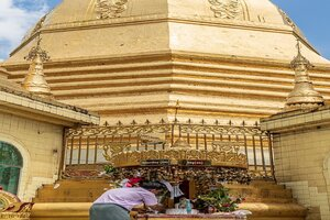 Man making offering to altar in Sule Pagoda