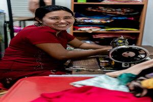 ミシンの横で微笑む女性