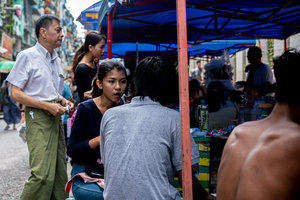 Young woman having meal in food stall
