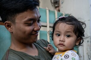 Father and his little daughter in the lane of Jakarta