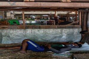 藁屑の上で寝る男