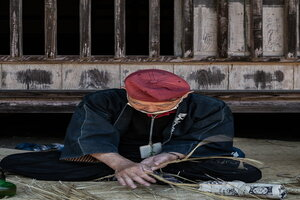 Man making a rope by twisting straw