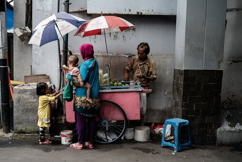Parent and children shopping at a fruit stall