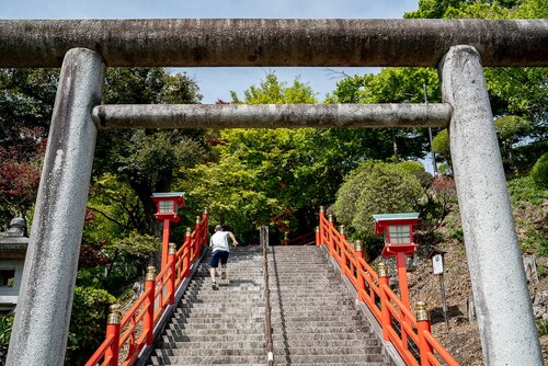 High schoolboy running up the stone steps of Orihime Shrine